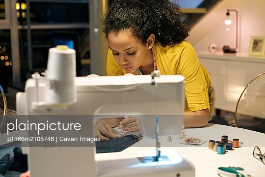 Female entrepreneur measuring jeans on table in office - p1166m2105748 by Cavan Images