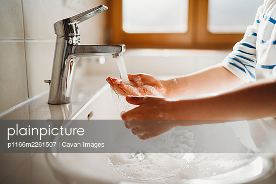 Close up of young hands being washed with soap - p1166m2261507 by Cavan Images