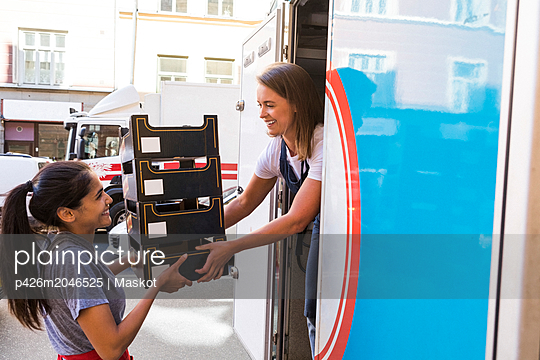 Smiling female colleagues loading food truck with containers in city - p426m2046525 by Maskot