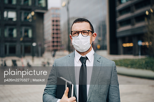 Male entrepreneur with diary in office park during pandemic - p426m2270327 by Maskot
