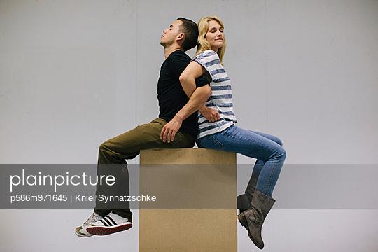 Junges Paar sitzt Rücken an Rücken - p586m971645 von Kniel Synnatzschke