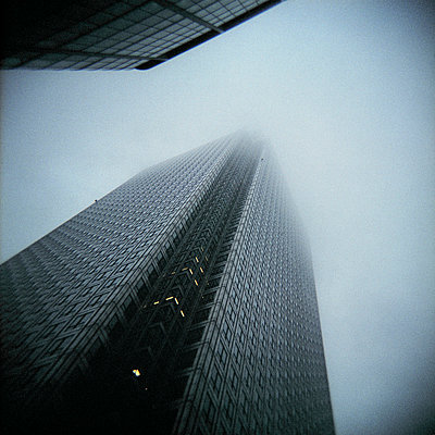 Low angle view of Canary Wharf Tower in mist - p1072m829290 by Neville Mountford Hoare