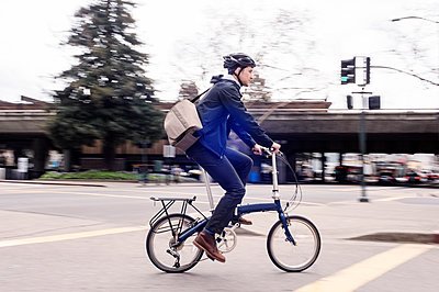 Side view of businessman riding bicycle on city street - p1166m1140219 by Cavan Images