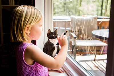 Side view of girl writing on window glass while standing by kitten at home - p1166m1526920 by Cavan Images