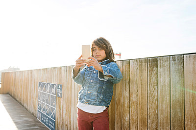Young boy taking a selfie with a smart phone on a rooftop in barcelona - p1166m2084933 by Cavan Images