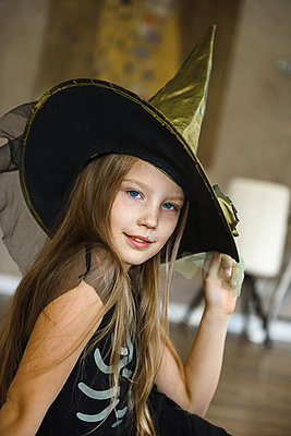 Smiling Teenage Girl in Hat Dressed for Halloween in Witch Costume - p1166m2147248 by Cavan Images