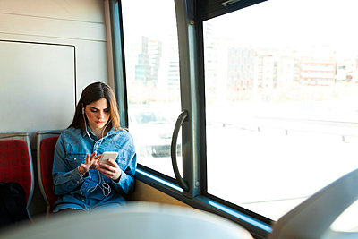 Young woman sitting in bus listening music with cell phone and earphones - p300m1587849 by Valentina Barreto
