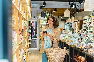 Young woman shopping in a food shop - p300m2118617 by VITTA GALLERY
