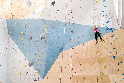 Woman climbing on the wall in climbing gym - p300m2169872 by Hernandez and Sorokina