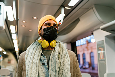 Man wearing protective face mask and headphones looking away while standing in train - p300m2251073 by Ezequiel Giménez
