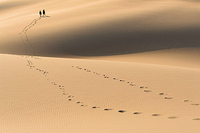 A young couple hiking through sand dunes at sunset - p343m1443384 by Brandon Huttenlocher