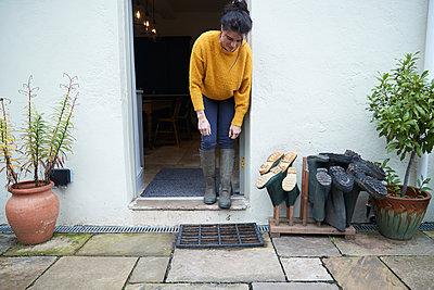 Woman in doorway beside wellies - p429m2023260 by Peter Muller