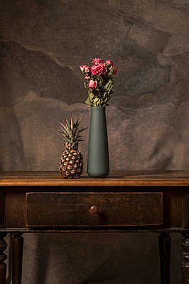 A pineapple alongside vase of roses on sideboard - p947m2178577 by Cristopher Civitillo