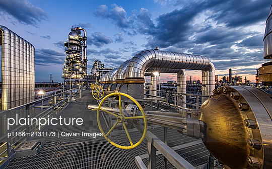 Sunset as viewed through pipe in a refinery - p1166m2131173 by Cavan Images
