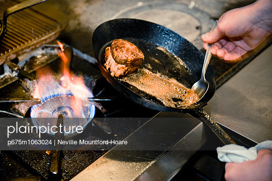 Chef basting meat cut with pan juice - p675m1063024 by Neville Mountford-Hoare