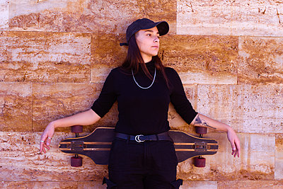 Young skater girl dressed in black leaning with her skate on a w - p1166m2255851 by Cavan Images