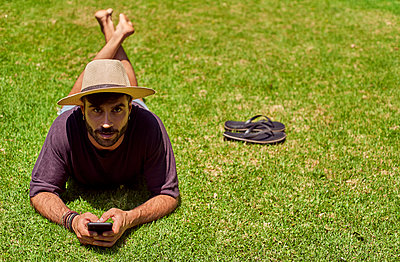 Man lying in grass using his smartphone - p300m2156747 by Veam