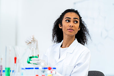 Young female doctor holding liquid flask while looking away in laboratory - p300m2266236 by Giorgio Fochesato