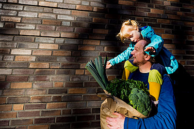 Father talking to daughter carried on shoulder while holding vegetables bag - p300m2275455 by Irina Heß