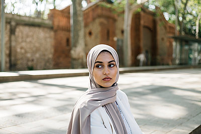 Young woman wearing hijab looking away while sitting on footpath - p300m2282668 by Xavier Lorenzo