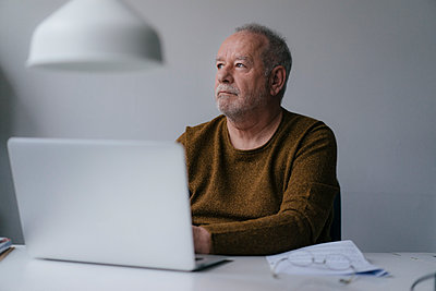 Elderly man at desk - p586m2089141 by Kniel Synnatzschke