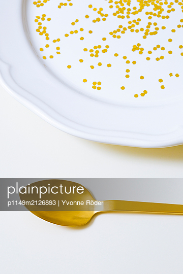 Goldener Löffel neben dekoriertem Teller - p1149m2126893 von Yvonne Röder