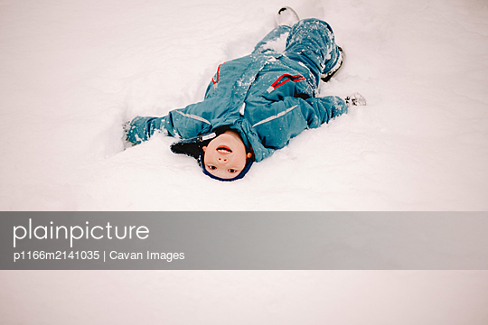 Cheerful boy with mouth open lying in snow during winter - p1166m2141035 by Cavan Images