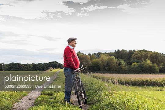 Senior man with bicycle in rural landscape - p300m2069593 by Uwe Umstätter