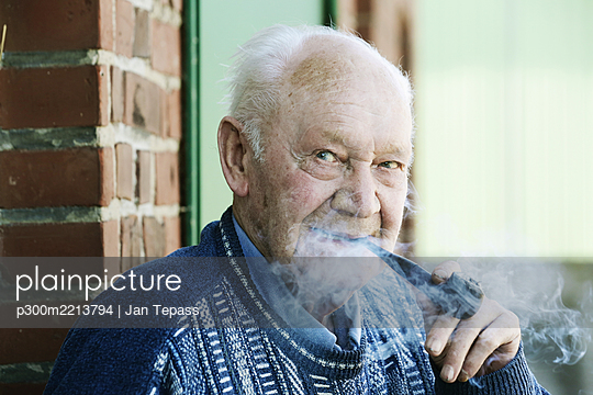 Germany, Portrait of senior man holding pipe, close up - p300m2213794 by Jan Tepass