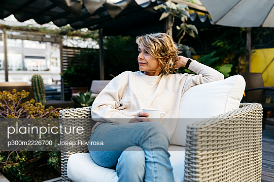 Mature woman looking away while holding coffee cup sitting at rooftop - p300m2226700 by Josep Rovirosa