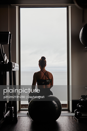 Woman on fitness ball looking through window - p312m2191230 by Dayfotografi