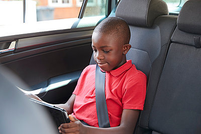 Boy using digital tablet in back seat of car - p1023m2238488 by Himalayan Pics