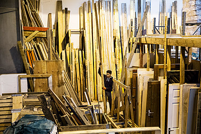 Interior view of warehouse with stacks of wooden planks, young man working. - p1100m1575744 by Mint Images