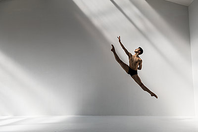 Dancer jumps with legs outstretched - p1139m2173418 by Julien Benhamou