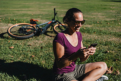 Smiling woman using mobile phone while sitting by electric mountain bike at park - p300m2240158 by David Molina Grande