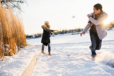 Sweden, Vasterbotten, Umea, Young couple enjoying snowball fight - p352m1142040 by Matthew Phillips