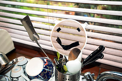 Kitchen sink draining board with utensil pot holding sieve with tape attached creating a happy face illusion - p1047m2210908 by Sally Mundy