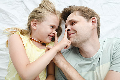 Father happy smiling daughter in bed - p300m2274379 by Ekaterina Yakunina