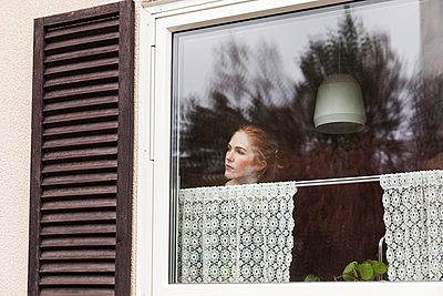 Woman looking through window while standing at home - p426m1179220 by Maskot