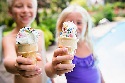 Caucasian children eating ice cream near swimming pool - p555m1421662 by JGI/Jamie Grill
