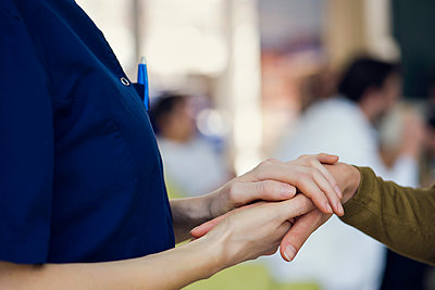 Healthcare worker holding patient's hand - p623m1447765 by Frederic Cirou