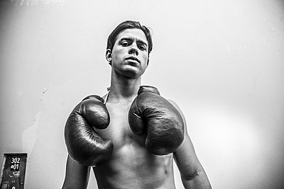 Young man with boxing gloves  - p975m1466274 by Hayden Verry