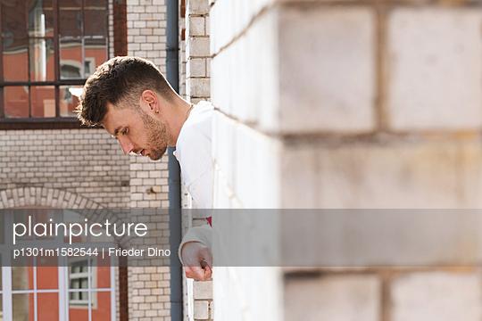 Mann lehnt sich aus einem Fenster  - p1301m1582544 von Delia Baum