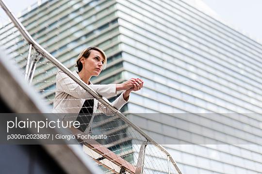 Businesswoman leaning on railing looking at distance - p300m2023887 von Giorgio Fochesato