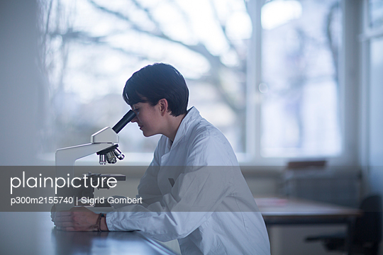 Female chemist looking through a microscope - p300m2155740 by Sigrid Gombert