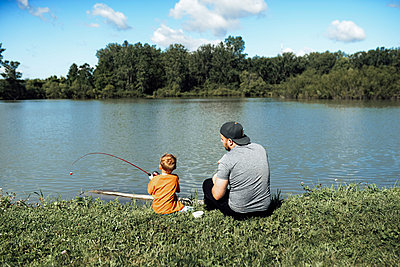 Rear view of son fishing while sitting with father at lakeshore against sky - p1166m2001056 by Cavan Images