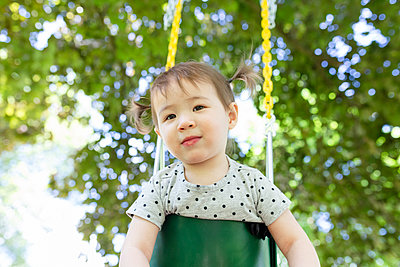 Adorable Toddler Girl with Ponytails Looks While Sitting in Swing - p1166m2218379 by Cavan Images