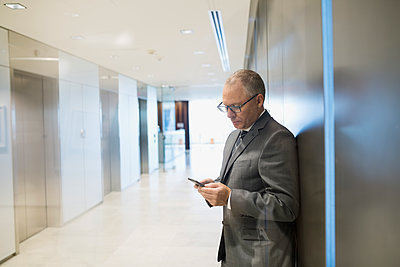 Businessman texting in office corridor - p1192m1183763 by Hero Images