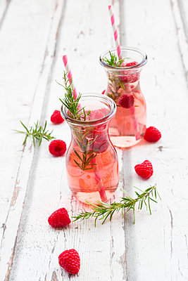 Two glass bottles of homemade raspberry lemonade flavoured with rosemary - p300m1587178 von Larissa Veronesi