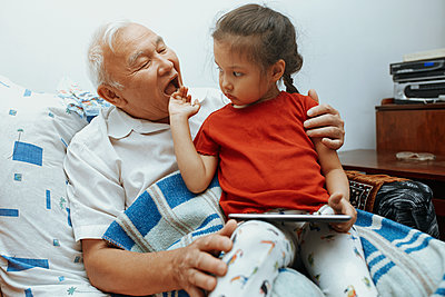 Girl sitting on grandfather's lap with digital tablet at home - p300m2273713 by Arman Zhenikeyev